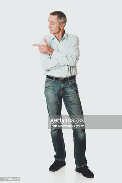 Mature Man Pointing While Standing Against White Background