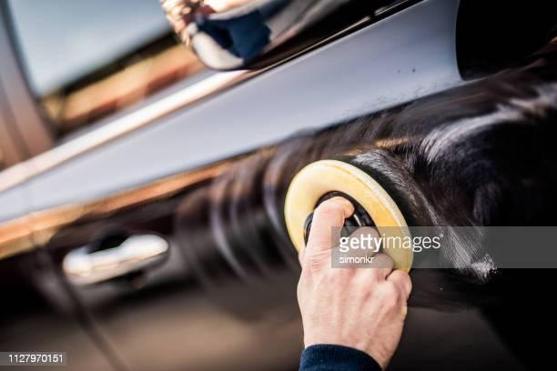 homem maduro, polimento carro com almofada do aplicador - reluzente - fotografias e filmes do acervo
