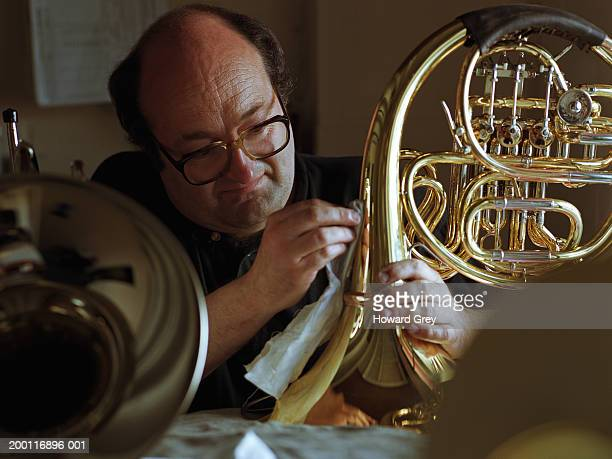 Mature man polishing french horn, close-up
