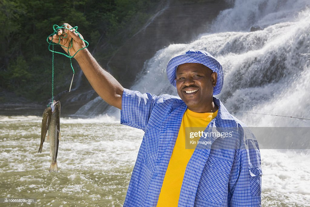 Mature man posing with fish, waterfall in background : Foto stock