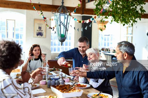 mature man pouring wine at dinner table - 50 54 years stock pictures, royalty-free photos & images