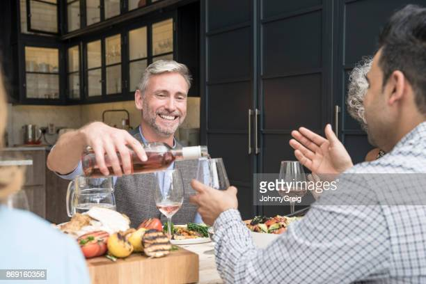 Mature man pouring wine for male friend at dinner table