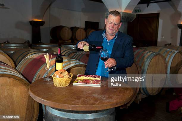 Mature Man Pouring Wine in Old Cellar, Europe