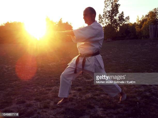 Mature Man Practicing Karate While Standing On Field Against Sky During Sunset