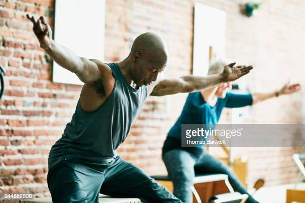 Mature man practicing on pilates chair during class in fitness studio
