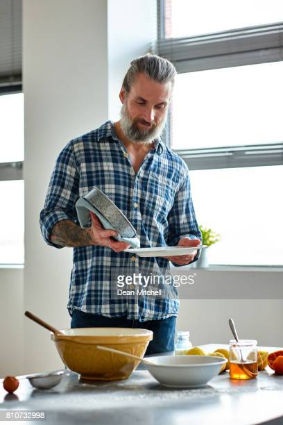mature man preparing cake at home - one mature man only stock pictures, royalty-free photos & images