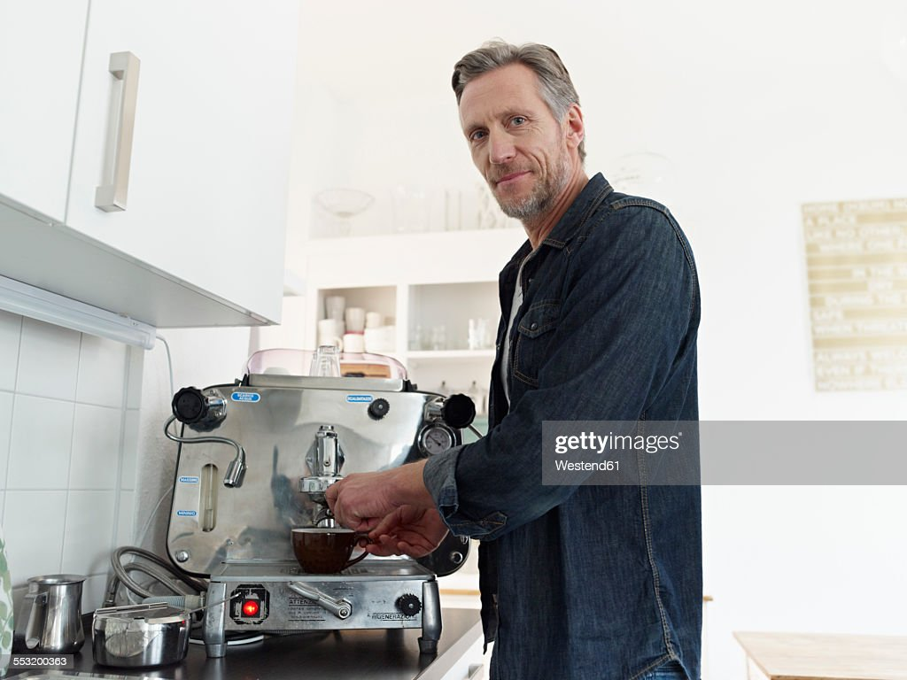 Mature man preparing espresso with espresso machine : Stock Photo