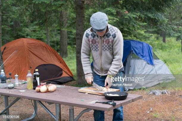 Mature man preparing food on campsite, Washington, USA