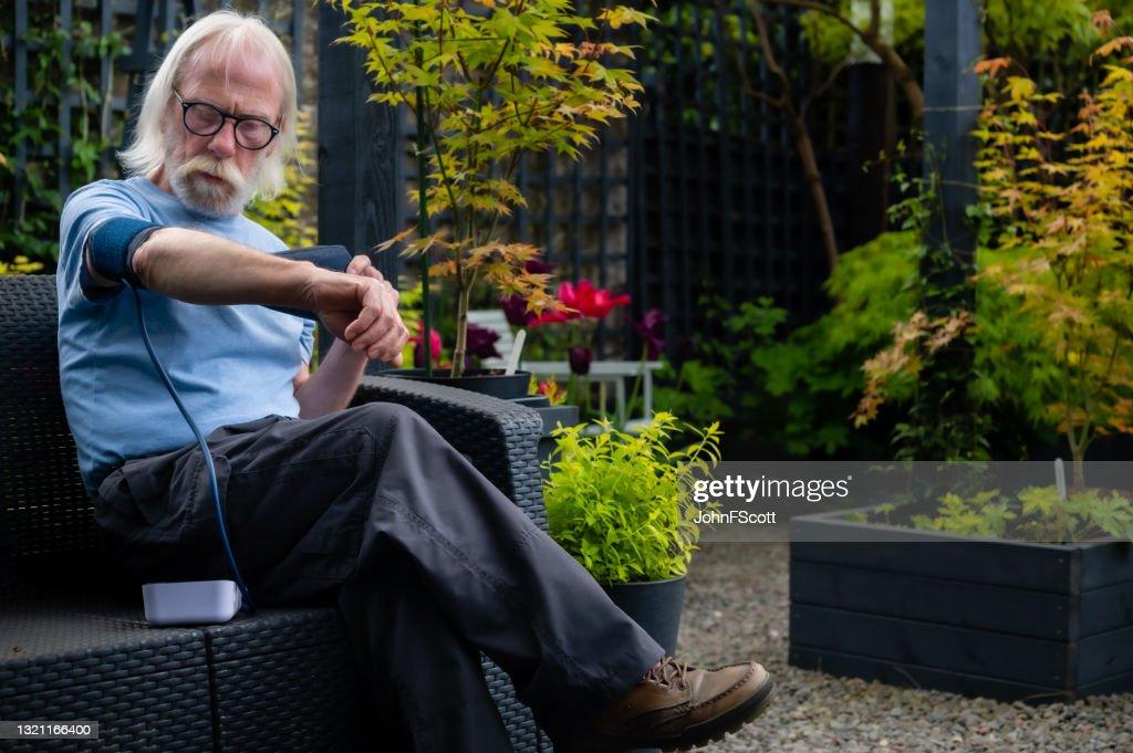 Mature man preparing to check his blood pressure : Stock Photo