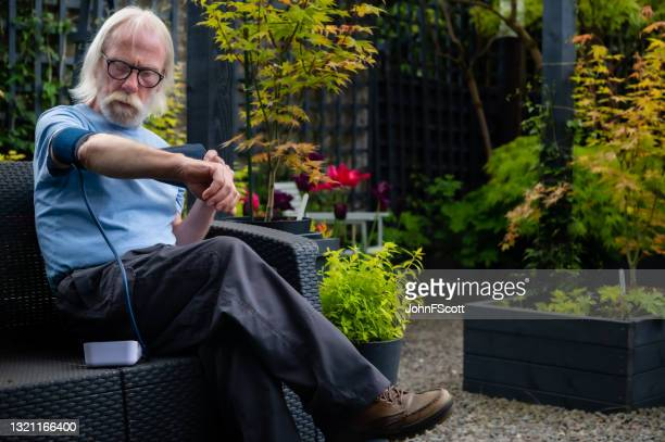 mature man preparing to check his blood pressure - johnfscott stock pictures, royalty-free photos & images