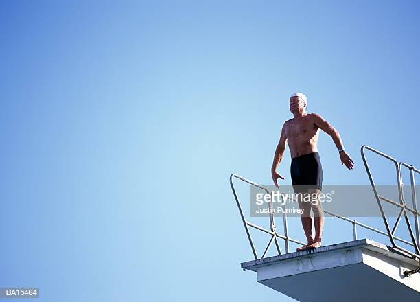 mature man preparing to dive off platform - anticipation stock pictures, royalty-free photos & images