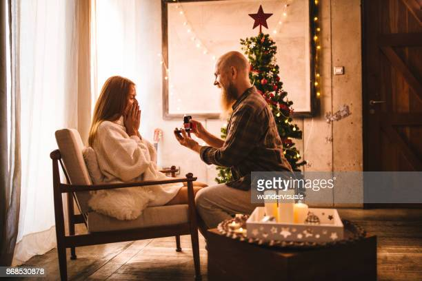 mature man proposing with engagment ring on christmas day - engagement ring box stock photos and pictures