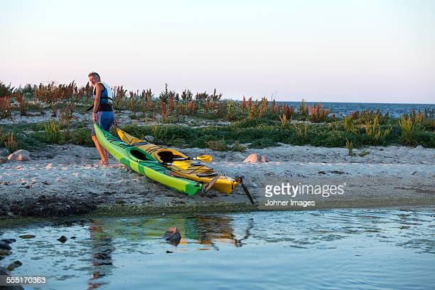 Mature man pulling kayaks