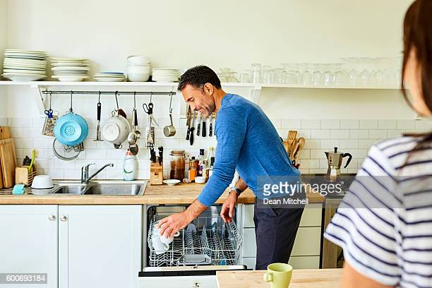 Mature man putting coffee mugs in dishwasher