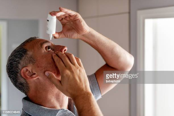 mature man putting eye drops in eyes - inserting stock pictures, royalty-free photos & images