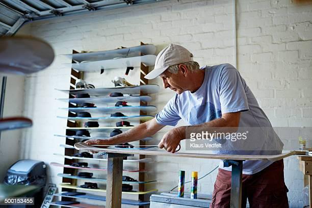 Mature man putting tape on sandboard, before paint