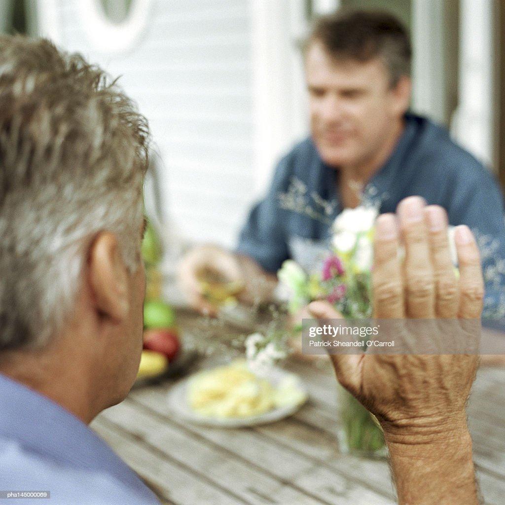Mature man raising hand, rear view, close-up : Stockfoto