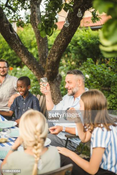 mature man raising wine glass while sitting with friend and children in backyard party - garden party stock pictures, royalty-free photos & images