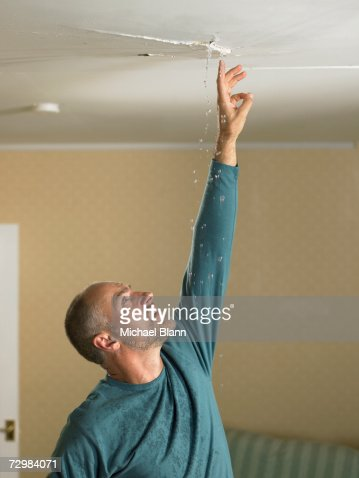 Mature Man Reaching Up To Touch Water Falling From Crack