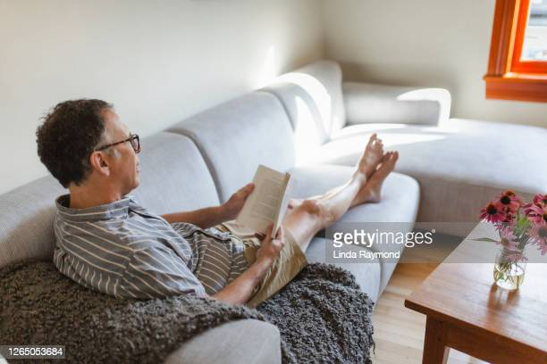 mature man reading a book on a sofa - 20th century style stock pictures, royalty-free photos & images