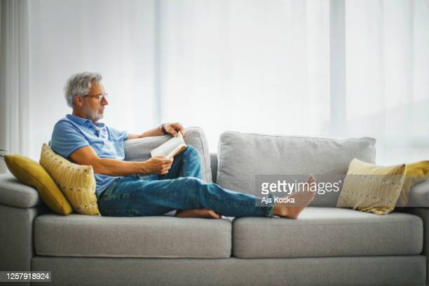mature man reading a book on the sofa. - reading stock pictures, royalty-free photos & images