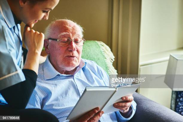 mature man reading a book with home caregiver - hospice stock pictures, royalty-free photos & images