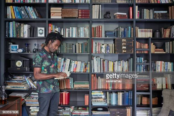 mature man reading book by shelves - literature stock pictures, royalty-free photos & images