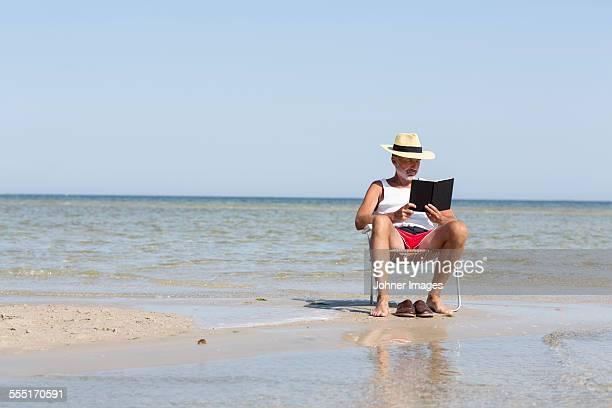 mature man reading book on beach - エーランド ストックフォトと画像