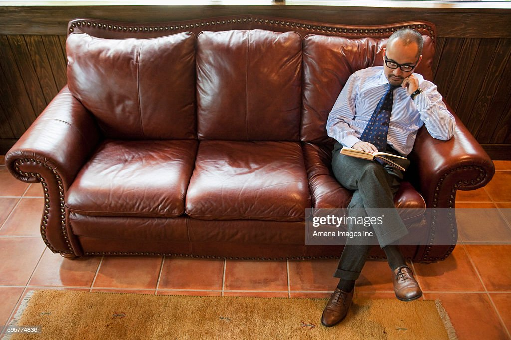 Mature Man Reading Book On Leather Sofa Stock Photo Getty Images