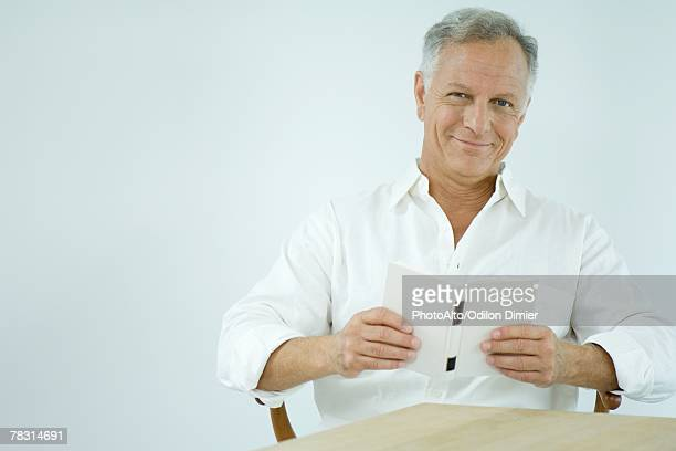 mature man reading book, smiling at camera - open collar stock pictures, royalty-free photos & images