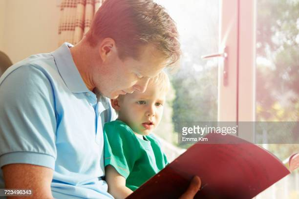 Mature man reading book to son on his lap