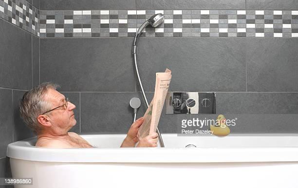 Mature man reading financial paper in bath