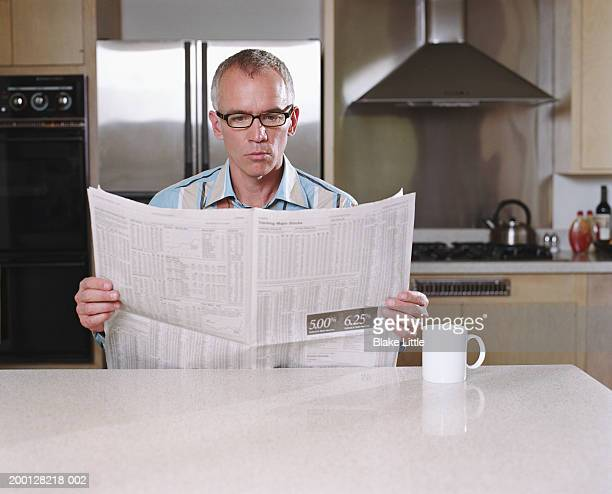 Mature man reading financial section of newspaper in kitchen