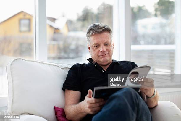 Mature man reading magazine at home