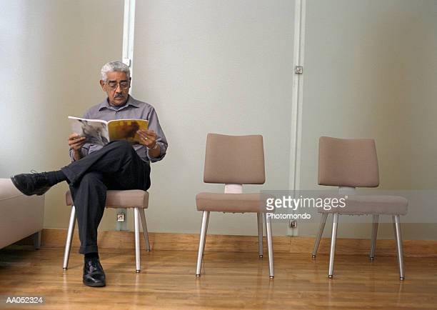 mature man reading magazine in waiting room - treats magazine fotografías e imágenes de stock