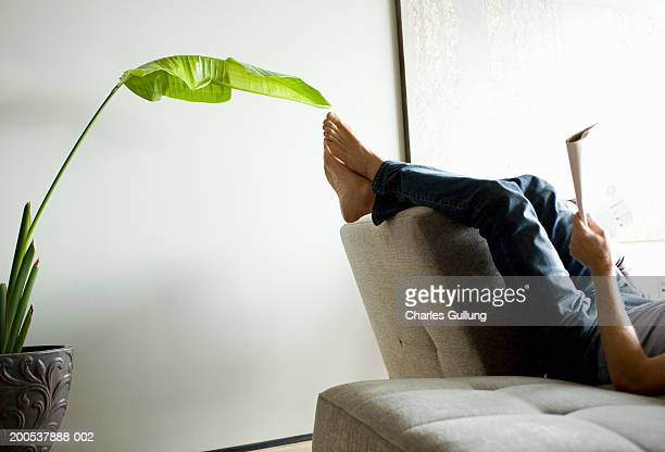 mature man reading magazine on sofa, low section, side view - feet up stock pictures, royalty-free photos & images