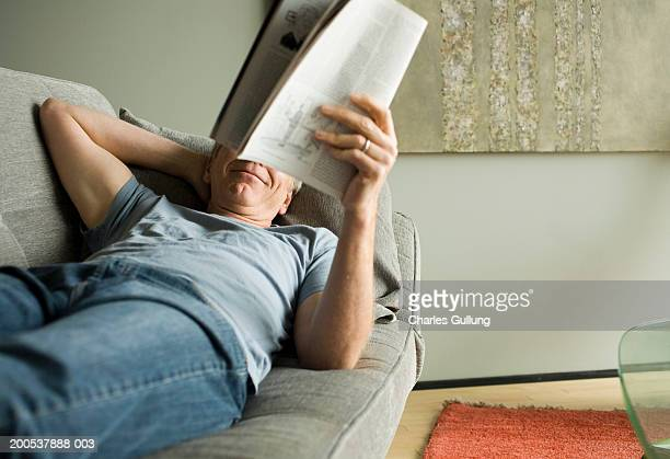 Mature man reading magazine on sofa, smiling, hand behind head