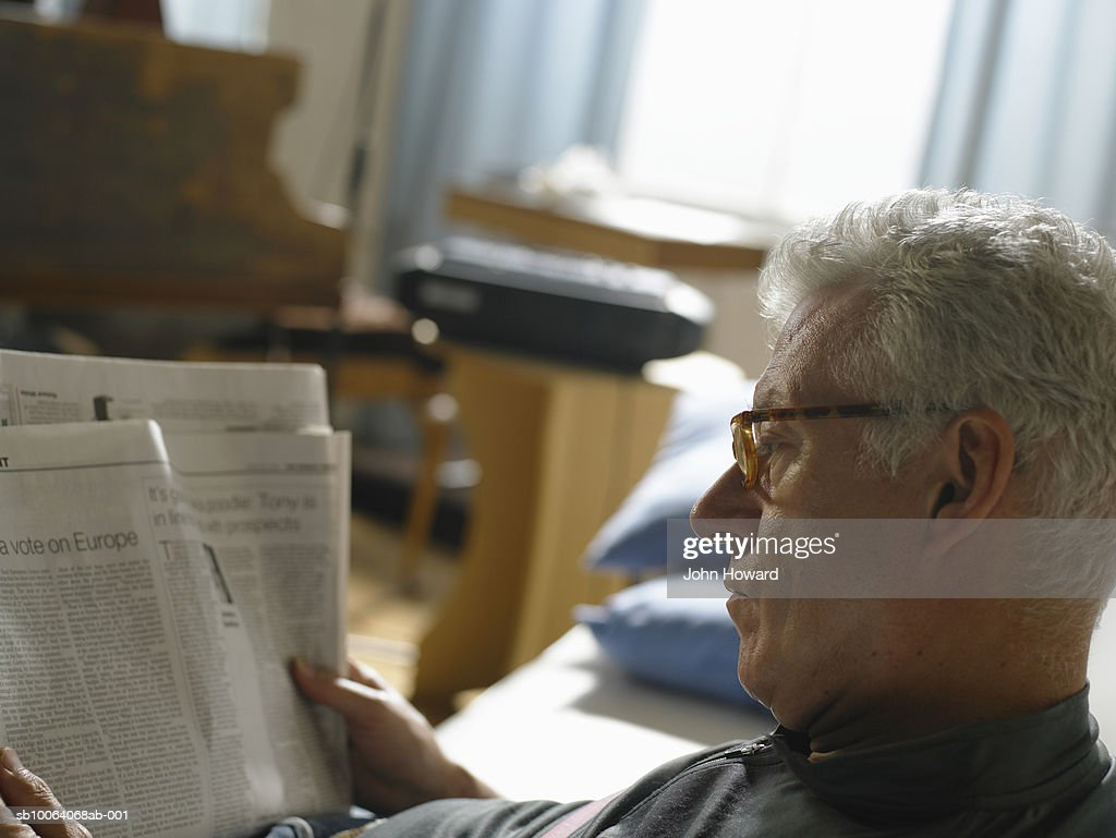 Mature man reading newspaper, close up : Stock Photo