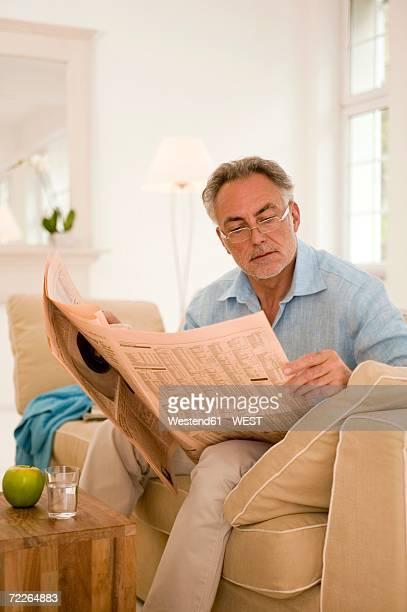 Mature man reading newspaper on sofa