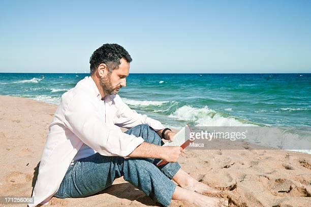 Maduro hombre leyendo en la playa