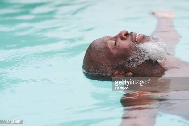 a mature man relaxes in a pool - serene people stock pictures, royalty-free photos & images