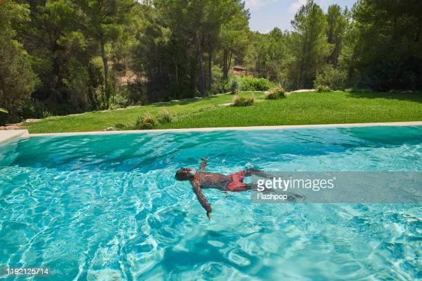 a mature man relaxes in his pool - flotter sur l'eau photos et images de collection