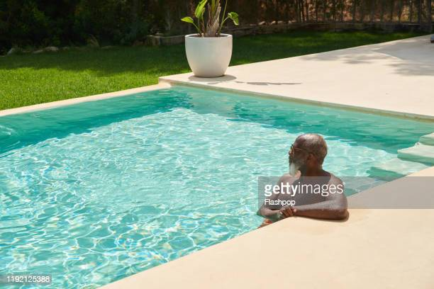 a mature man relaxes in the pool - poolside stock pictures, royalty-free photos & images