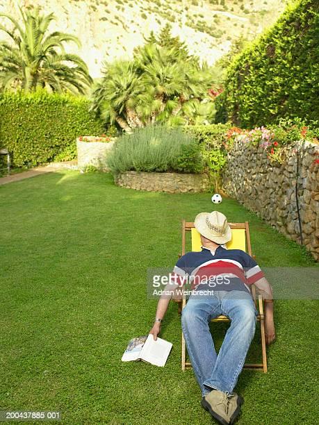 Mature man relaxing in deckchair in garden, hat covering face