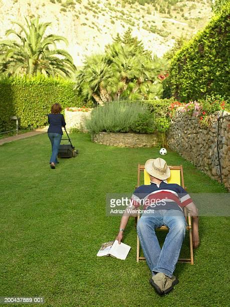 Mature man relaxing in deckchair in garden, mature woman mowing lawn