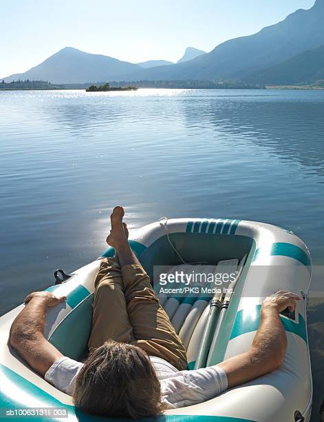 Mature man relaxing in inflatable raft on lake, mountain range in background