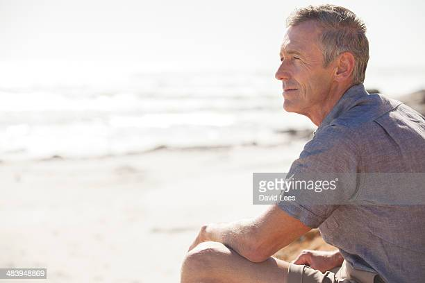 mature man relaxing on beach - three quarter length stock pictures, royalty-free photos & images