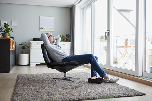 Mature man relaxing on leather chair in his living room - gettyimageskorea