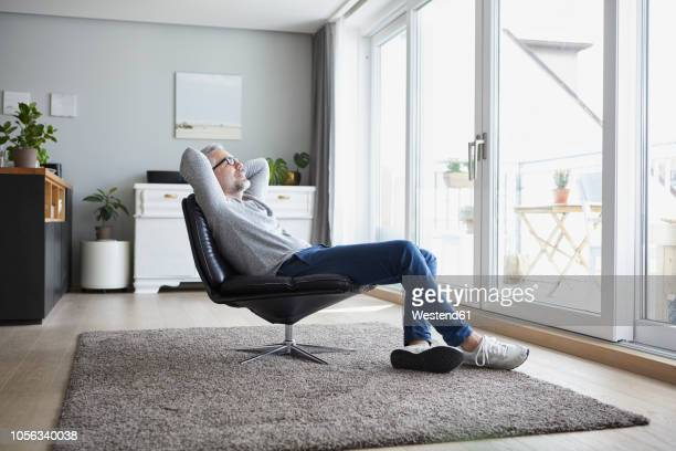 mature man relaxing on leather chair in his living room - sitting foto e immagini stock