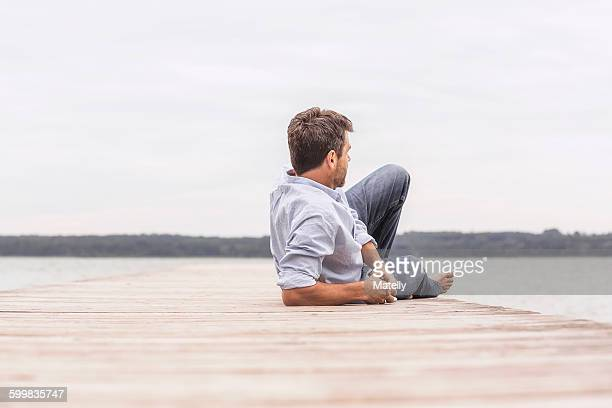 Mature man relaxing on pier, rear view